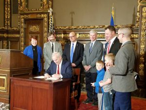 Senator Eken stands with advocates of the Rural Finance Authority Bill as Governor Dayton signs it into law.