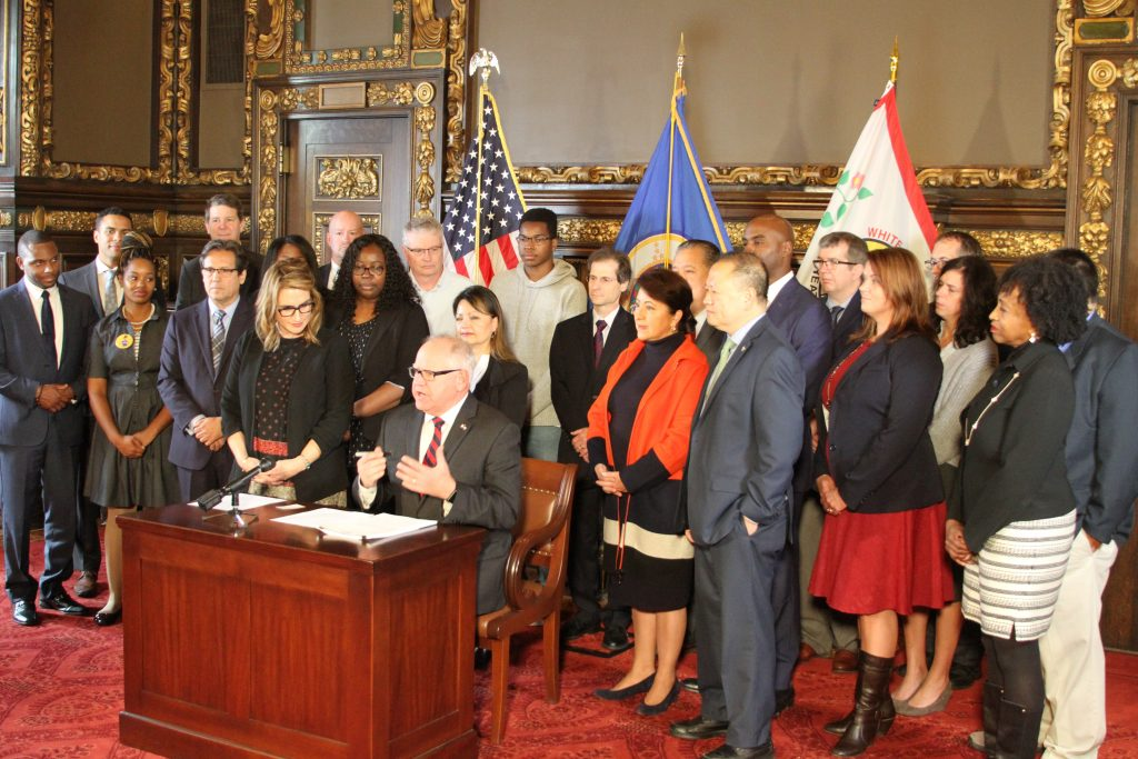 Photo of large group of individuals surrounding Governor Walz as he signs a bill. Photo cutline reads: Governor Tim Walz is joined by Senator Patricia Torres Ray and other advocates to witness her energy utilities diversity bill signed into law.
